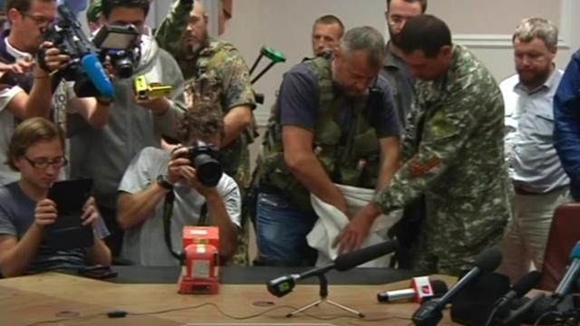 Ukrainian rebel hands over MH17's black boxes.  Image credit: Yahoo News