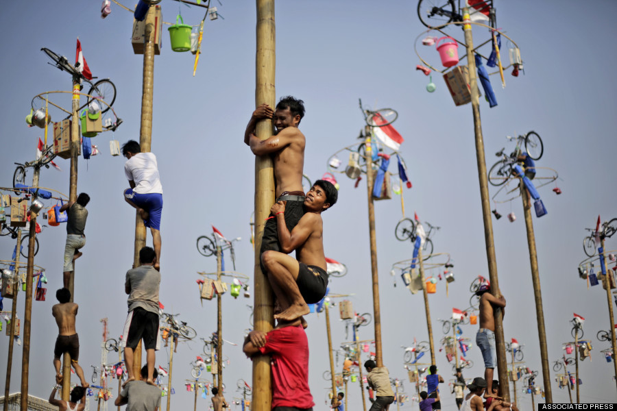 This could ALSO be you. Climbing a greased pole for PRIZES! YES! [Image Credit: Huffington Post]