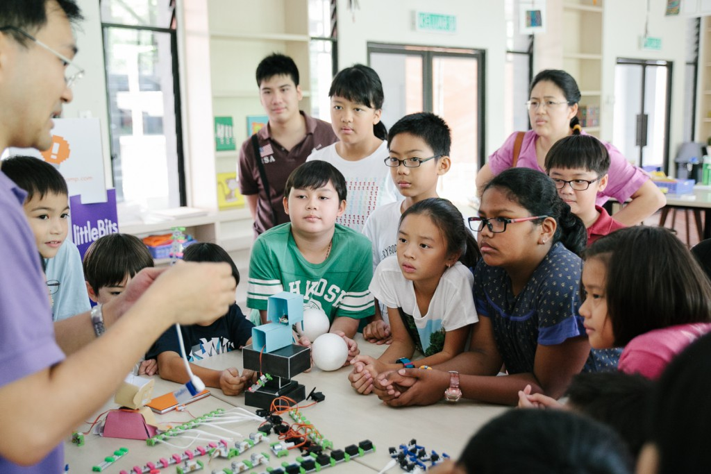 Students observing intently as Dr Ewe Chun Te demonstrates the different functions of the electronic pieces. (Image Credit: Creative Tech Camp)