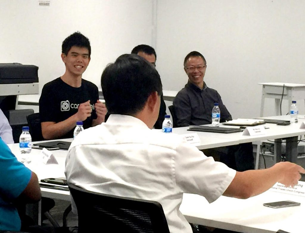 Quek Siu Rui of Carousell and Shaun Kwan of Trakomatic discussing their products with Mr Chan