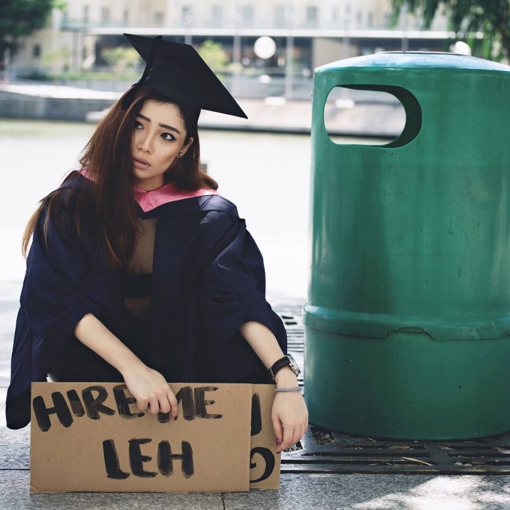 "Elizabeth in her graduation gown next to the dustbin with a ""Hire me leh"" sign/ Image credit:Alexander Ian Lo"